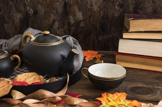 Libros antiguos cerca de juego de té y hojas