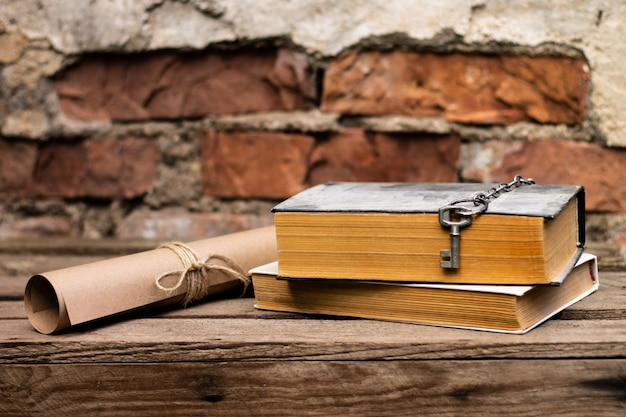 Libros antiguos con un desplazamiento y una tecla sobre una superficie de madera rústica sobre un fondo de pared de ladrillo.