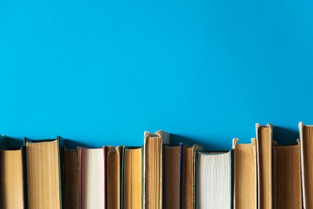 Libros antiguos en un estante con fondo azul.
