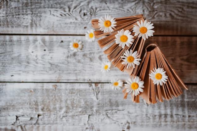 Libros antiguos con flores de margaritas blancas. . espacio libre para texto