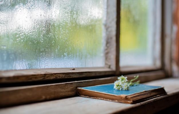 Libros antiguos en el fondo de la ventana húmeda de madera del pueblo