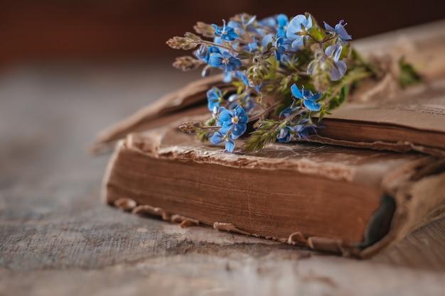 Libros antiguos con un ramo de flores silvestres de primavera
