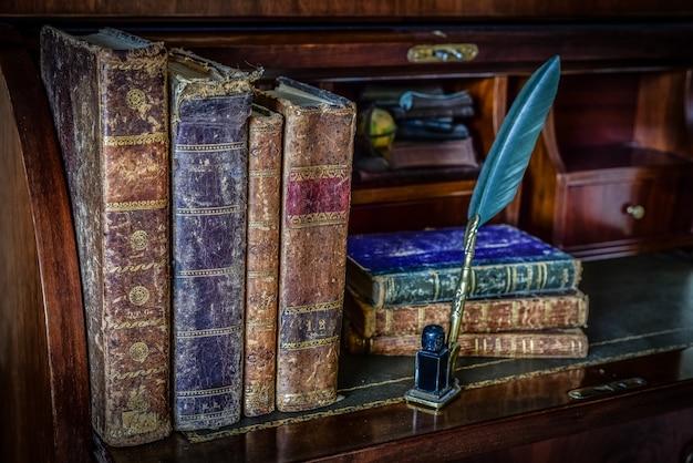 Libros antiguos sobre el escritorio y la pluma escribiendo