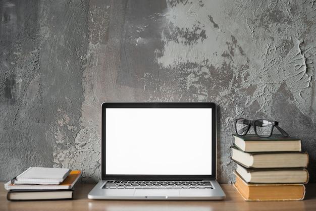 Libros apilados; gafas y laptop con pantalla blanca en blanco sobre superficie de madera.