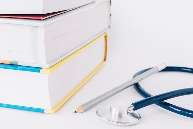 Libros apilados; lápiz y estetoscopio sobre superficie blanca.