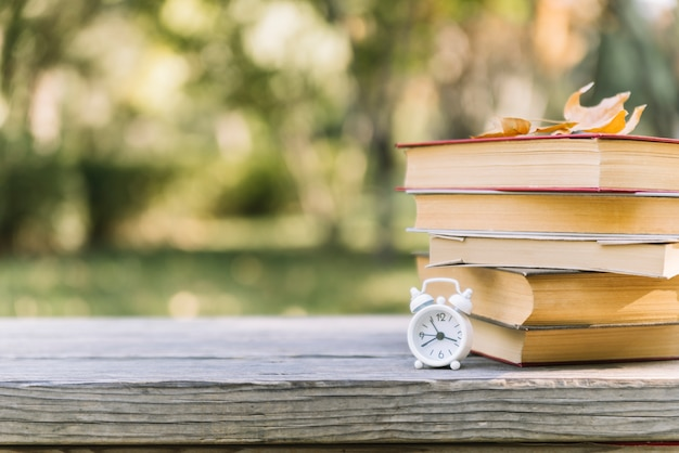 Libros apilados con reloj en una mesa