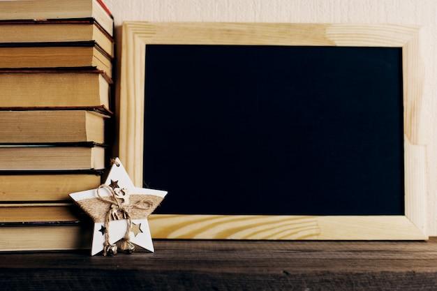 Libros y un árbol de navidad con conos, y una decoración de estrellas en un viejo estante de madera.