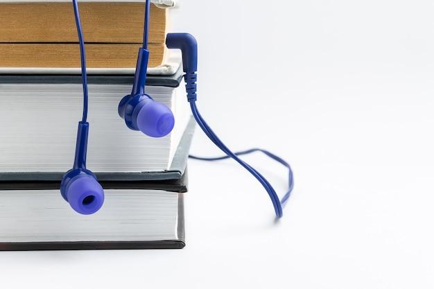 Libros y auriculares en blanco fundamento. concepto de audiolibro