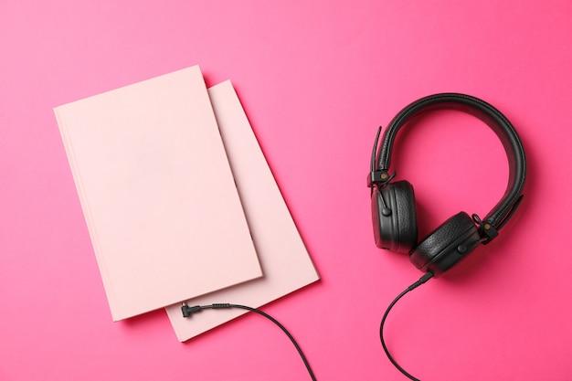 Libros y auriculares en espacio rosa, espacio para texto