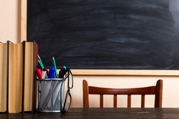 Libros, bolígrafos, lápices y vasos sobre una mesa de madera, contra una pizarra.