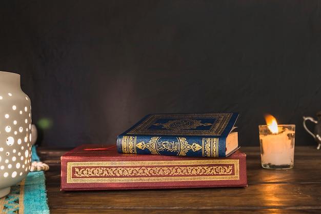 Libros cerca de linterna y vela