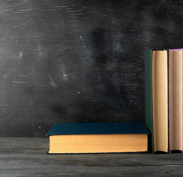 Libros cerrados con hojas amarillas sobre un fondo de pizarra negra