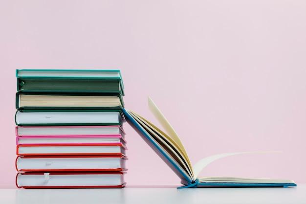 Libros coloridos con arreglo de fondo rosa