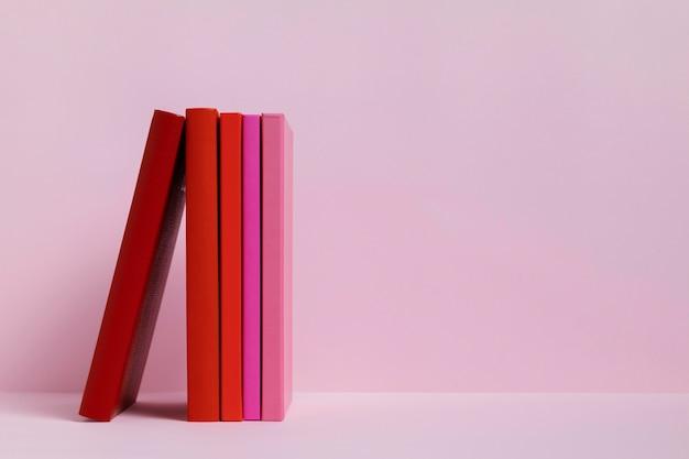 Libros coloridos con fondo rosa