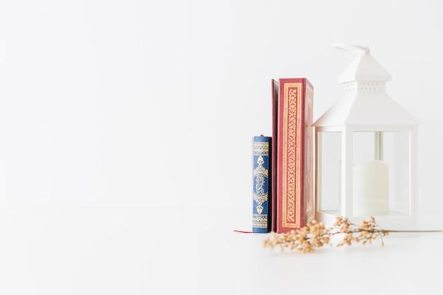 Libros del corán con linterna y rama