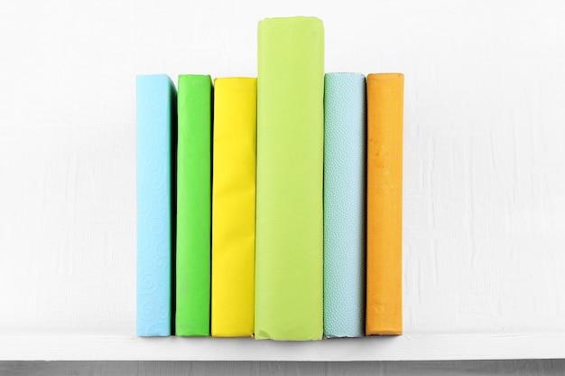 Libros cubiertos de colores en la estantería y pared blanca