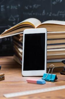 Libros escolares y artículos de papelería sobre una madera y un fondo de pizarra escrito con fórmulas y ecuaciones matemáticas