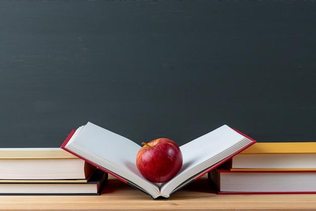 Libros escolares, manzana, pizarra con copyspace.