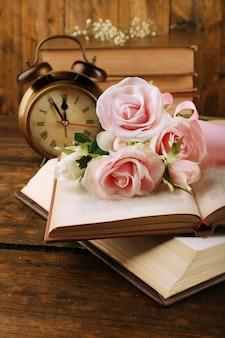 Libros con flores y reloj sobre superficie de madera
