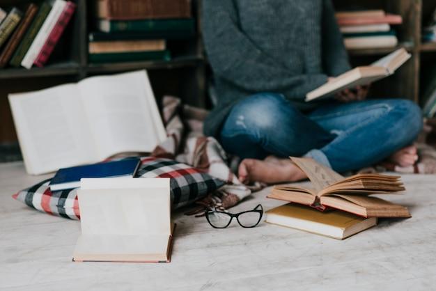 Libros y gafas cerca de mujer leyendo