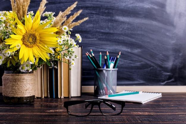 Libros, gafas, marcadores y un ramo de flores en un jarrón sobre blanco