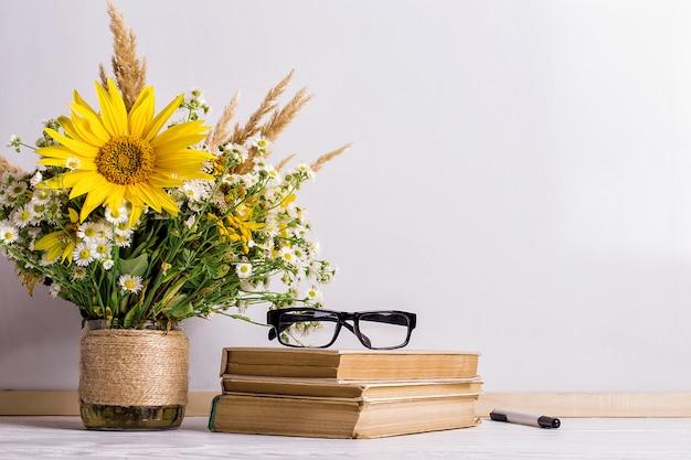 Libros, gafas, marcadores y un ramo de flores en un jarrón sobre pizarra blanca