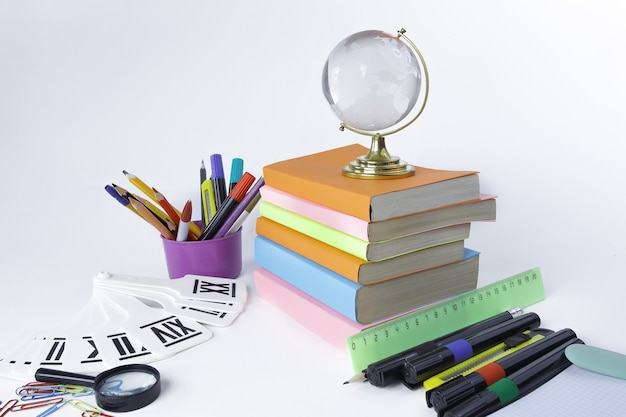 Libros de globo de cristal y útiles escolares sobre fondo blanco.