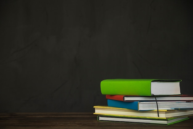 Libros gráficos en la mesa junto a la pared negra