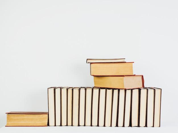 Libros hermosos del vintage con páginas amarillas en una tabla blanca