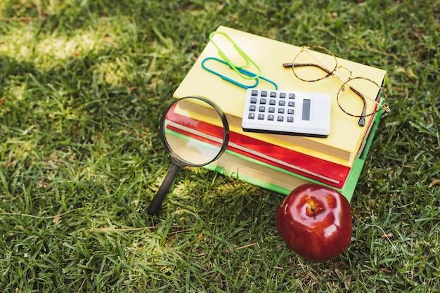 Libros con implementos ópticos, calculadora y manzana sobre hierba.