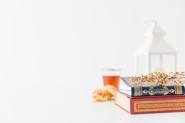 Libros islámicos con linterna y rama
