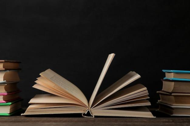 Libros y libro desplegado sobre una mesa de madera marrón y sobre un fondo negro. libros viejos. educación. colegio. estudio