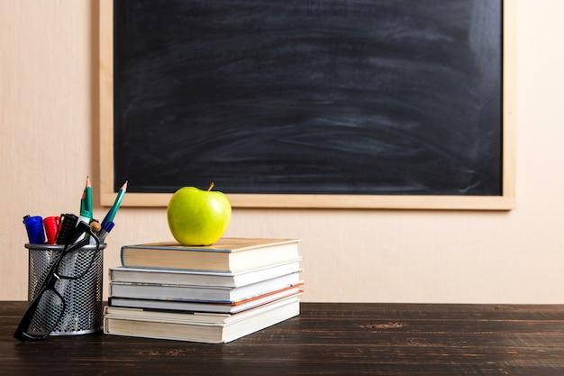 Libros, manzanas, bolígrafos, lápices y vasos sobre una mesa de madera, contra una pizarra.