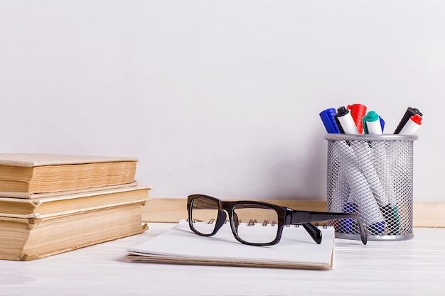 Libros, marcadores, libreta, lápiz y vasos sobre la mesa.