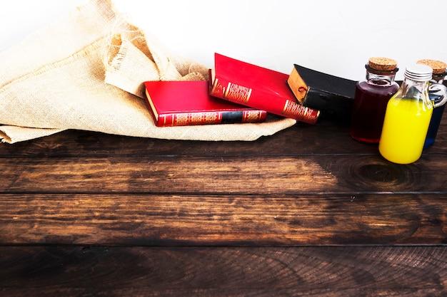 Libros con material de lino y pociones en el escritorio