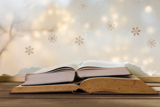 Libros en mesa de madera cerca de banco de nieve, copos de nieve y luces de colores