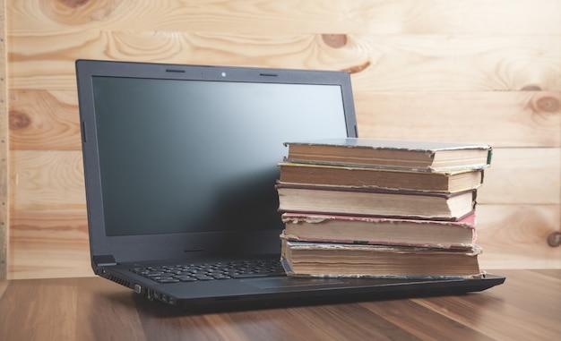 Libros y portátil en la mesa de madera internet education business