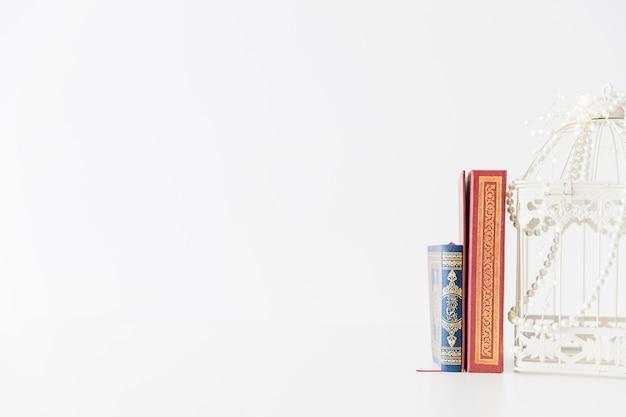 Libros religiosos de pie con jaula de pájaro