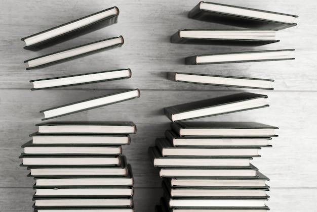 Libros sueltos cayendo, fondo claro en blanco y negro.