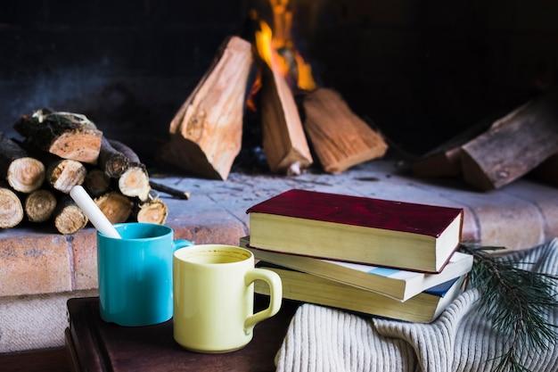 Libros y tazas junto a la chimenea.