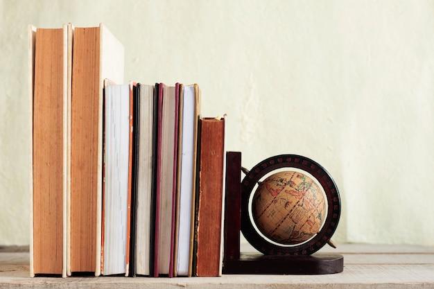 Libros de texto y globo en madera.