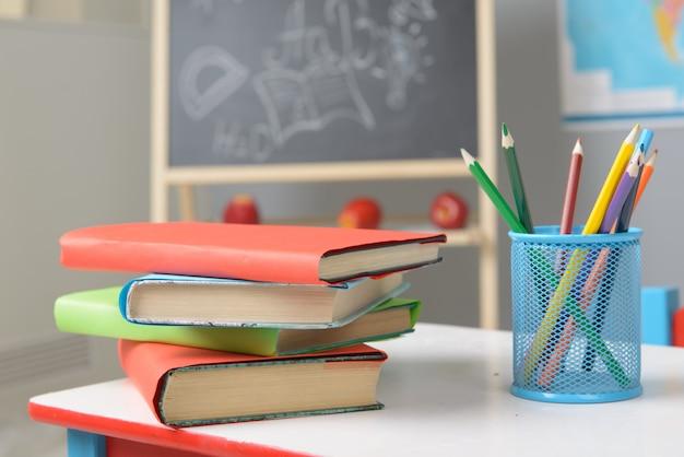Libros de texto y lápices de colores en el escritorio de la escuela.