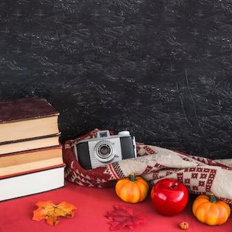 Libros y frutas falsas cerca de la manta y la cámara