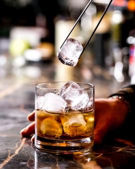 La licitación de barra agrega hielo con un clip de acero en una copa