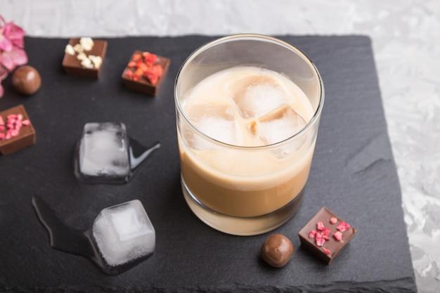 Licor de chocolate dulce con hielo en vidrio y pizarra de piedra negra. vista lateral
