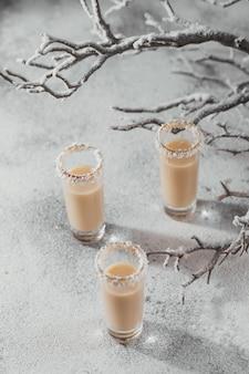 Licor de crema irlandesa o licor de café con corona de copos de coco en la parte superior de un vaso corto. decoraciones navideñas whinter