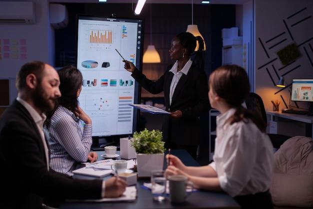 Líder afroamericano adicto al trabajo de pie frente al monitor de presentación explicando los pr ...