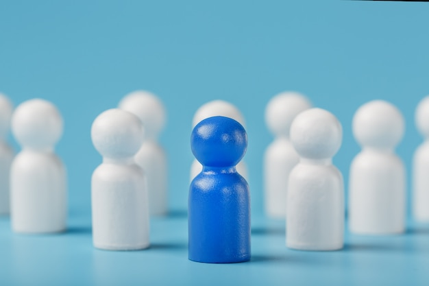 Líder azul el líder lidera a un grupo de empleados en blanco para lograr la meta, el personal y el reclutamiento. el concepto de liderazgo.