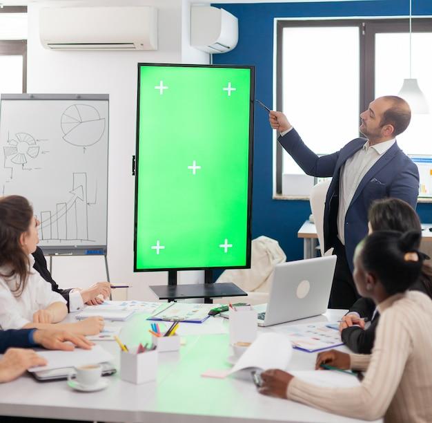 Líder de la empresa que presenta el plan financiero utilizando una pantalla de maqueta frente a una lluvia de ideas de diversos equipos