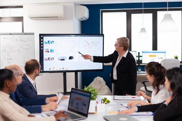 Líder de la empresa senior de intercambio de ideas en la sala de conferencias el personal corporativo discutiendo la nueva aplicación comercial con colegas mirando la pantalla